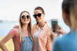 leisure and friendship concept - happy smiling teenage girls or best friends in sunglasses being photographed by smartphone at seaside in summer