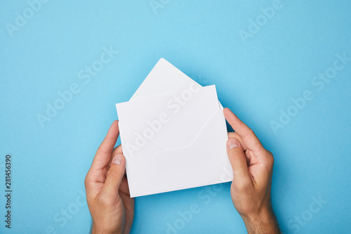 Cuadros en Lienzo cropped view of man holding envelope with blank white card on blue background