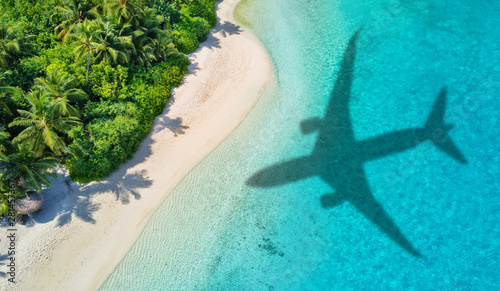Travel concept with airplane shadow and beach - fototapety na wymiar