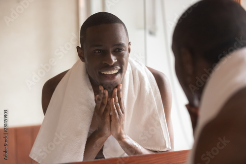 African man looking in mirror cleaning face after shaving Canvas Print