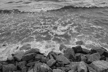 Waves Hitting Rock Barrier In Black And White