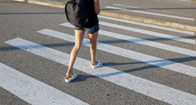 Legs Of A Girl Walking Along A Pedestrian Crossing
