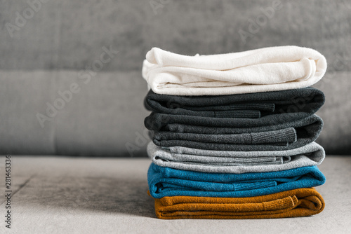 Fotografía  Pile of sweaters on the gray couch. Men's textile clothing.