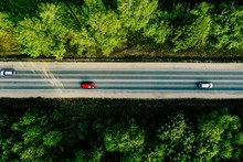 Aerial View Of Cars Driving Through The Forest On Country Road.