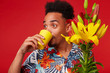 Close up of young surprised African American man in Hawaiian shirt, looks away and drinking water from a yellow glass, holds yellow and red flowers bouquet, stands over red background.