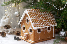 Gingerbread House And Christmas Trees On A Luminous Background. Bokeh Effect.