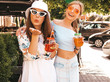 Two young beautiful smiling hipster girls in trendy summer clothes and panama hat.Sexy carefree women posing in the street.Positive models having fun in sunglasses.Drinking fresh cocktail smoozy drink