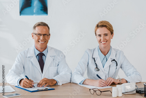 cheerful doctors looking at camera and smiling while sitting near table