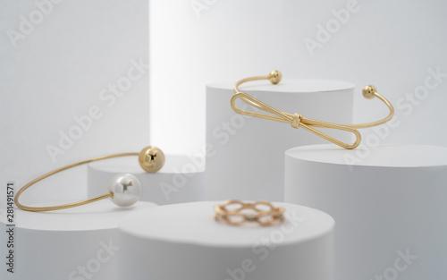 Fotografía  Modern golden bracelets and ring on white cylinders setup
