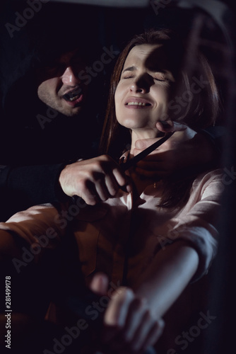 Fototapeta thief strangling beautiful frightened woman in automobile at night with knife
