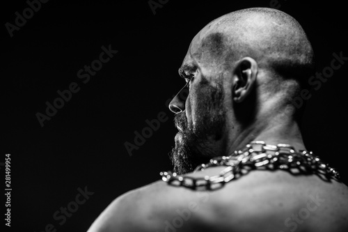 Fotografiet  black and white portrait of a brutal man tearing the chain