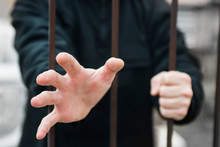 Man's Hand Stretches Through The Bars Locked Man In A Cage Cell. Hand Of A Refugee Behind Fence