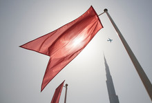 Low Angle View Of Red Flag Waving Against Clear Sky