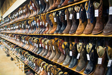 View Of Brown And Black Leather Cowboy Boots On Shelves In Shop