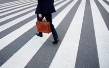 Low Section Of Businessman Walking On Pedestrian Crossing