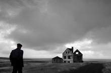 Rear View Of Man Looking At Abandoned Farmhouse
