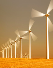 View Of Wind Turbines Spinning In Field