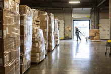 Side View Of Man Pulling Trolley With Cardboard Boxes In Distribution Warehouse