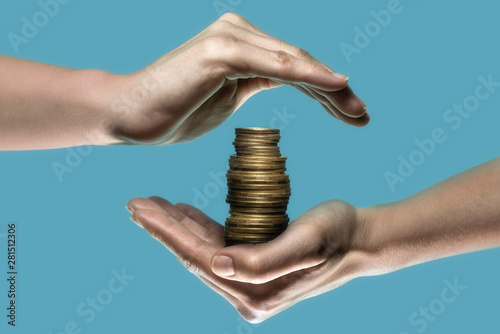 Fototapeta Stack of coin are protected by woman hands. Concept safe custody of cash. Image obraz