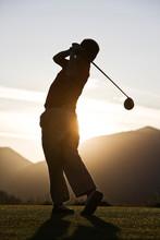 Senior Golfer Teeing Off At Sunset