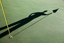 Shadow Of Golfer And Golf Flag On Golf Course