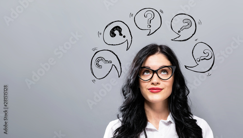 Photo Question marks with speech bubbles with young businesswoman in a thoughtful face
