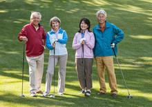 Senior Golfing Couple Standing On Golf Course