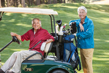Portrait Of Smiling Golfers On Golf Course