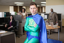 Portrait Of Businessman In Super Hero Costume With Colleagues In Background