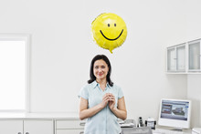 Portrait Of Smiling Woman Holding Smiley Face Balloon In Office