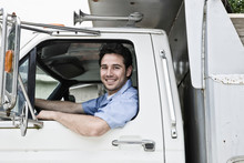 Portrait Of Smiling Driver Sitting In Delivery Truck