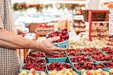 Midsection Of Man Holding Boxof Fresh Red Cherries In Market