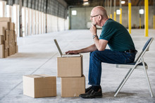 Side View Of Architect Working On Laptop In Warehouse