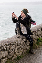 Young Woman Taking Photograph While Sitting On Stone Wall