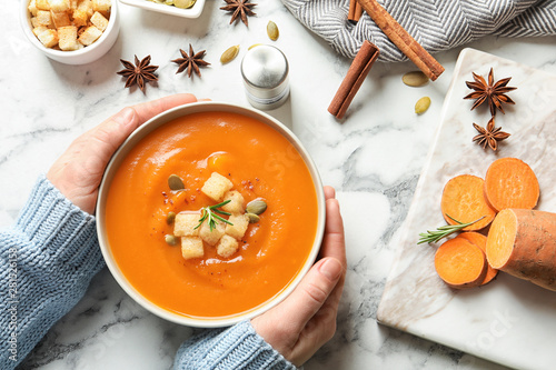 Woman with bowl of tasty sweet potato soup at table, top view Tablou Canvas