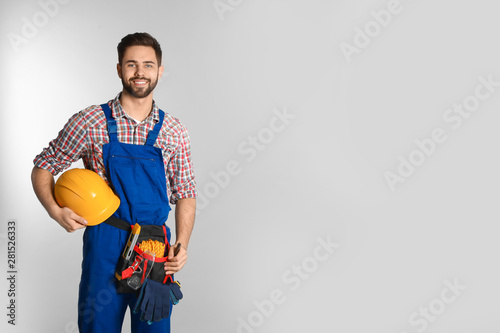 Papel de parede Portrait of construction worker with tool belt on light background