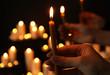 Leinwandbild Motiv Woman holding burning candle in darkness against blurred background, closeup