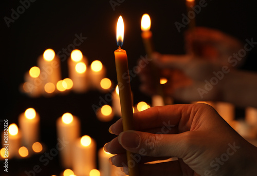 Obraz na plátně  Woman holding burning candle in darkness against blurred background, closeup