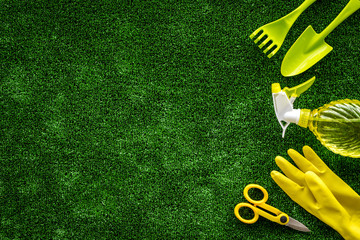 Gardening tools on green grass background top view mock up