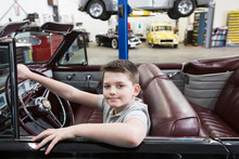 Portrait Of Boy Sitting In Convertible Car In Automobile Repair Shop
