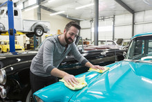 Mechanic Applying Wax On Car In Automobile Repair Shop