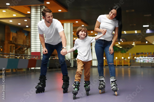 Happy family spending time at roller skating rink Canvas-taulu