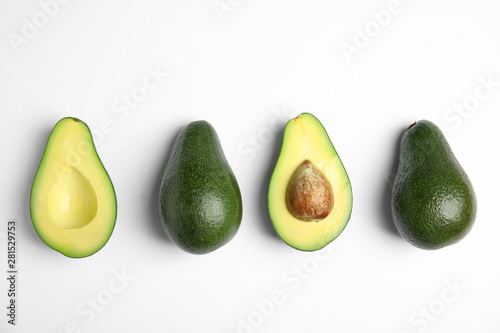 Fototapeta  Cut and whole fresh ripe avocados on white background, top view