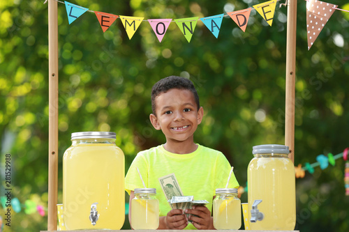 Fototapeta  Cute little African-American boy with money at lemonade stand in park