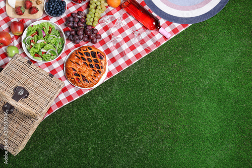 Wall Murals Picnic Flat lay composition with picnic basket and products on checkered blanket, space for text