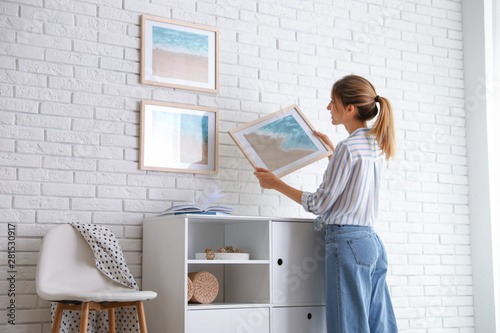 Fototapeta Decorator hanging picture on white brick wall in room. Interior design obraz