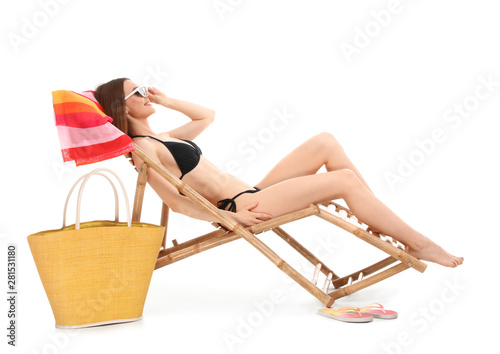 Fotografia, Obraz Young woman with beach accessories on sun lounger against white background