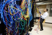 Frustrated Technician Pulling Cat 5 Cables In Server Room
