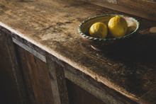 Close Up Of Lemons In Earthenware Bowl On Wooden Cabinet