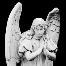 Guardian Angel Sculpture With Open Wings Isolated On Black Background. Angel Sad Expression Sculpture With Eyes Down And Hands Together In Front Of Chest. BW Photog. Non-modern Religious Statue.